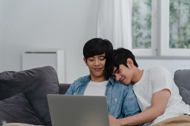 Молодые пары гомосексуалиста используя компьтер-книжку компьютера на современном доме. азиатские lgbtq + мужчины счастливы расслабиться весело, используя технологии, смотря фильмы в интернете вместе, лежа на диване в гостиной дома. Бесплатные Фотографии