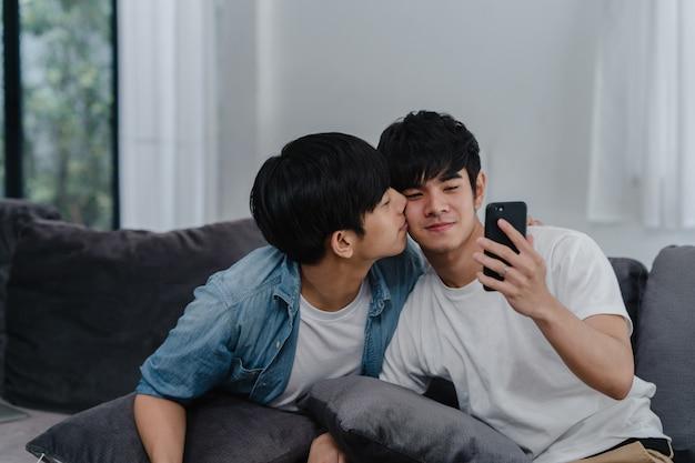 アジアのインフルエンサーゲイカップルのビデオブログを自宅で。アジアのlgbtqの男性は、リビングルームのソファに横たわっている間、ソーシャルメディアで技術携帯電話記録ライフスタイルビデオアップロードを使用して楽しいリラックスを楽しんでいます。 無料写真