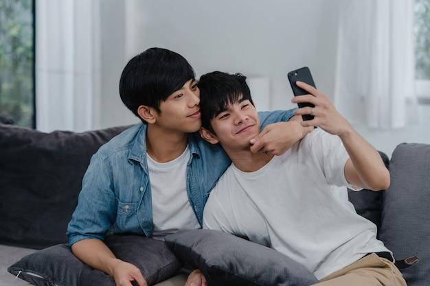 Азиатский влияющий гей-пара влог дома. азиатские люди lgbtq счастливые ослабляют потеху используя видео ролика образа жизни записи мобильного телефона технологии загружают в социальные медиа пока лежа софа в живущей комнате. Бесплатные Фотографии