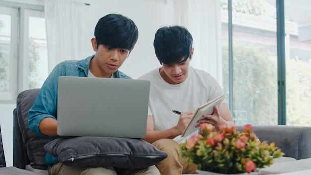 現代の家でラップトップを働く若いアジアゲイカップル。アジアlgbtq +の男性は、コンピューターを使用して、家のリビングルームでソファに横たわっている間インターネットで彼らの財政を一緒に分析して楽しくリラックスします。 無料写真