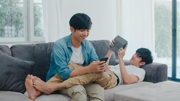 Молодые пары гомосексуалиста lgbtq используя мобильный телефон и таблетку на современном доме. азиатское счастливое мужское счастливое ослабляет технологию смеха и потехи игр играет совместно в интернете пока лежащ софа в живущей комнате. Бесплатные Фотографии