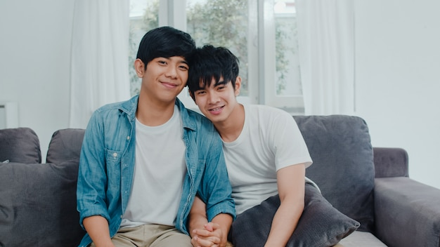 Пара молодых азиатских гей портрет чувство счастливой улыбкой на дому. азиатские люди lgbtq ослабляют зубастую улыбку смотря к камере пока лежащ на софе в живущей комнате дома в утре. Бесплатные Фотографии