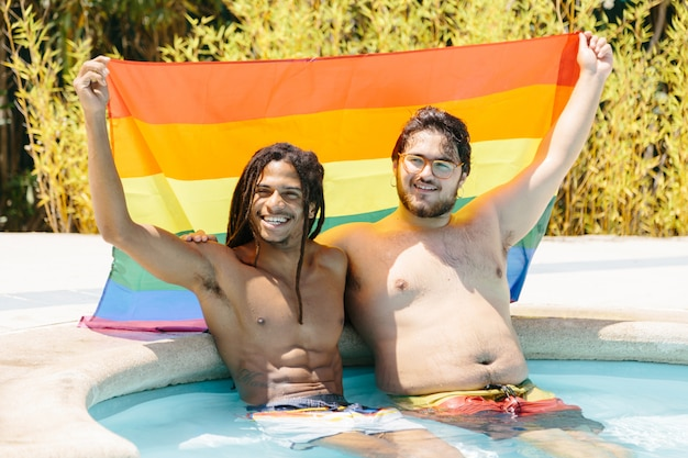 Мужчины, поднимающие флаг lgtb, сидя в бассейне Premium Фотографии