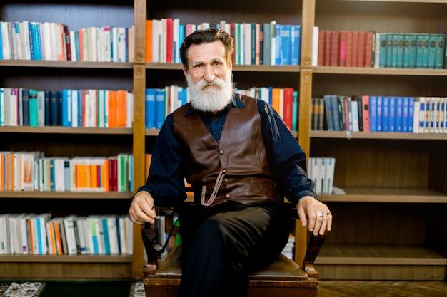 図書館で椅子に座っている暗いシャツとズボンと革のベストを身に着けている教員の司書、背景の書棚。知識、学習、教育のコンセプト Premium写真