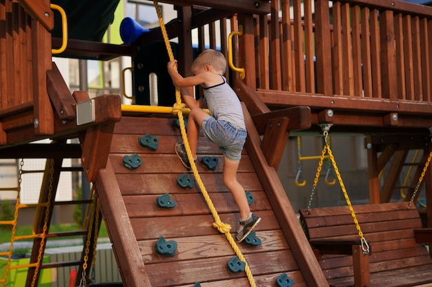 Life of children in a modern city, little boy is having fun on the playground near the house Premium Photo