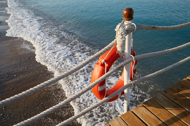 Lifebuoy with a rope is at the edge of water on the beach Premium Photo