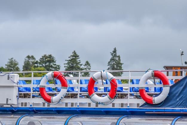 赤と白のlifebuoysは雨の後に曇った背景とボートに、 Premium写真