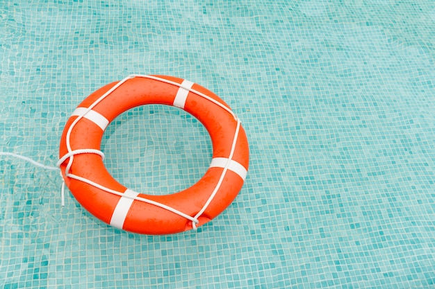 Lifeguard floating in swimming pool Premium Photo