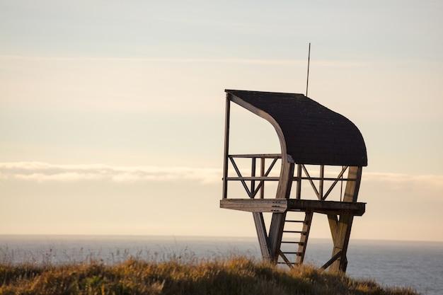 Torre bagnino in un campo circondato dal mare sotto un cielo nuvoloso la sera Foto Gratuite
