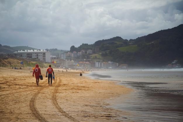 美しい空のビーチを歩いていくライフガード 無料写真