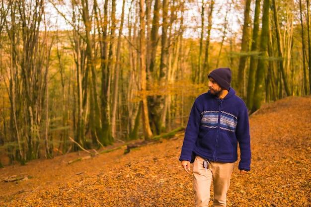 ライフスタイル、秋の森を楽しむ青いウールのセーターを着た若い男。バスク地方、ギプスコア、サンセバスティアンのアルティクツァの森。スペイン Premium写真