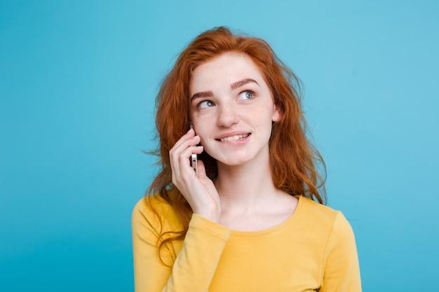 ライフスタイルとテクノロジーのコンセプト - 明るく幸せな生姜赤毛の少女の肖像画は、携帯電話で友人と楽しいとエキサイティングな話をしています。青いパステルの背景に隔離されています。スペースをコピーします。 無料写真