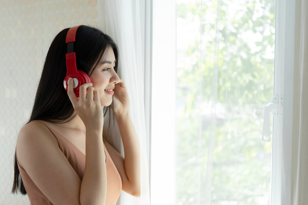Lifestyle beautiful asian woman cute girl  feel happy enjoy listening to music with earphones headphones on white bedroom Free Photo