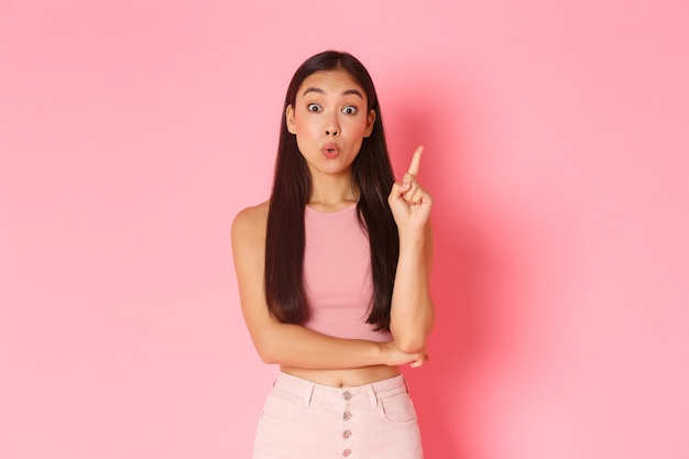 Концепция образа жизни, красоты и женщин. креативная привлекательная азиатская девушка в летней одежде находит решение, поднимает указательный палец и говорит свою идею, придумывает отличный план, стоит на розовой стене Бесплатные Фотографии