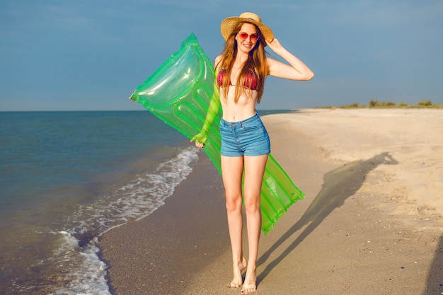 Lifestyle bright summer positive portrait of young pretty hipster woman having fun an the beach Free Photo