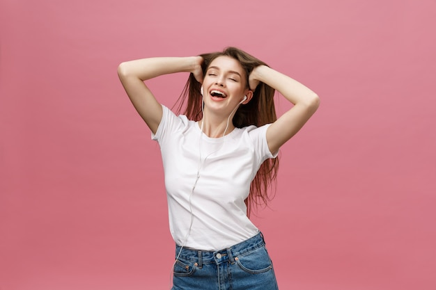 Lifestyle concept. young woman using phone for listening to music on pink background Premium Photo