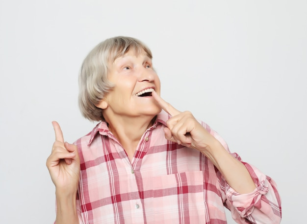 Lifestyle, emotion and people concept: aged grandmother with shocked face. portrait of grandmother with pink shirt. Premium Photo