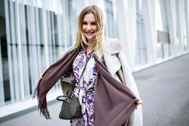 Образ жизни модный портрет довольно элегантной женщины в модном стильном наряде, фиолетовом длинном шарфе, роскошном кашемировом пальто и миди-платье, улыбающийся конец наслаждения, пребывание перед современным бизнес-центром Бесплатные Фотографии
