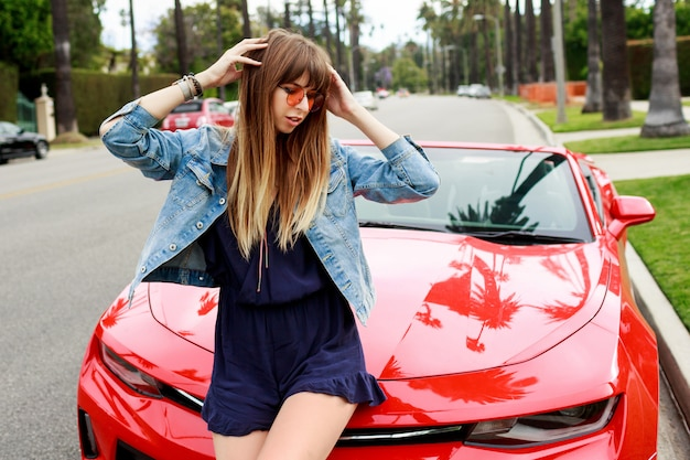 Lifestyle image of travel female sitting on the hood of amazing red convertible sport car. streets of los angeles. Free Photo