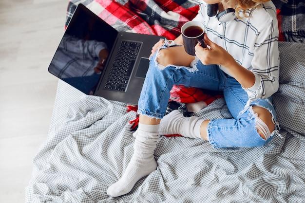 Immagine di stile di vita, donna che beve caffè e utilizza il computer, indossa calze calde e jeans alla moda. seduto sul letto. mattina presto. vista dall'alto. Foto Gratuite