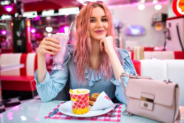 Образ жизни в помещении - образ стильной молодой красивой женщины с необычными волнистыми розовыми волосами и естественным макияжем, в милом голубом платье и джинсовой куртке, наслаждающейся своим вкусным американским ужином. Бесплатные Фотографии