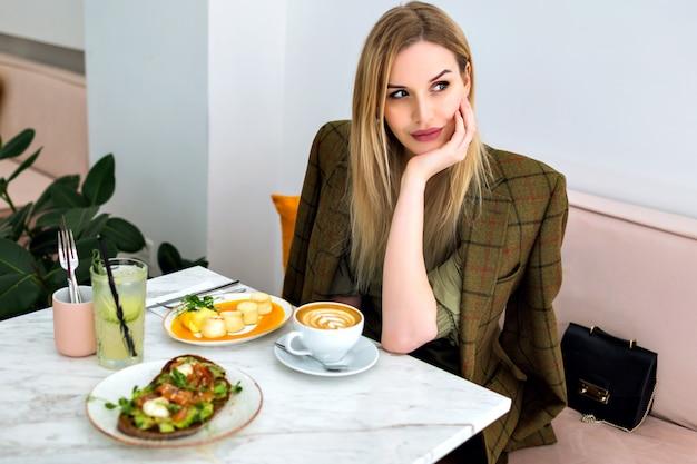流行に敏感なカフェでブランチを楽しんでいるウェイターを求めて、笑顔のスタイリッシュな若い金髪ビジネス女性のライフスタイル屋内ポートレート 無料写真
