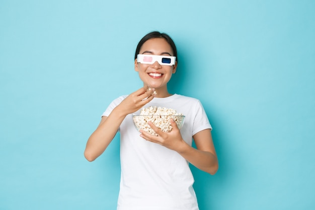 Lifestyle, leisure and emotions concept. smiling satisfied asian girl looking pleased while eating popcorn from bowl, watching movie on tv screen with 3d glasses, enjoying awesome series. Free Photo