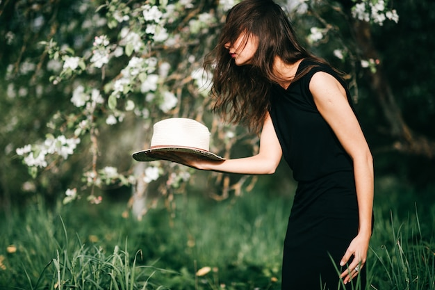 Lifestyle portrait of brunette girl in black dress with straw hat in her hands over blooming apple tree on background. Premium Photo