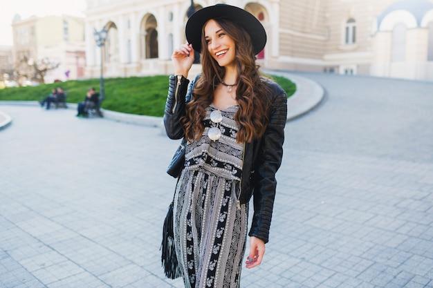 古いヨーロッパの都市で休日を楽しんでいるかなり陽気な女性のライフスタイルの肖像画。ストリートファッションルック。スタイリッシュな春の装い。 無料写真