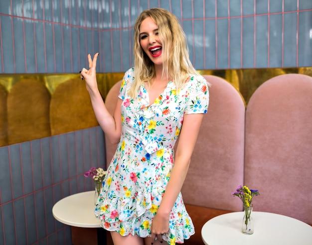 Образ жизни портрет довольно забавной блондинки-хипстера, позирующей в стильном ресторане, в мини-цветочном платье, улыбающейся, подмигивающей и показывающей науку своими руками, позитивного настроения. Бесплатные Фотографии