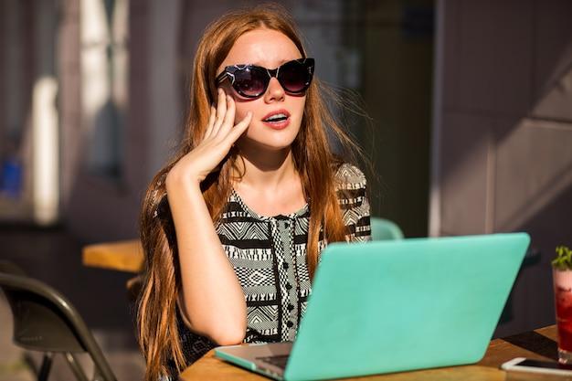 彼女のラップトップを使用して、カフェテラスに座っているかわいい学生赤毛の女の子のライフスタイルの肖像画 無料写真