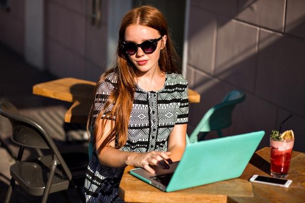 예쁜 학생 빨간 머리 소녀의 라이프 스타일 초상화, 그녀의 노트북을 사용하여 카페 테라스에 앉아 무료 사진