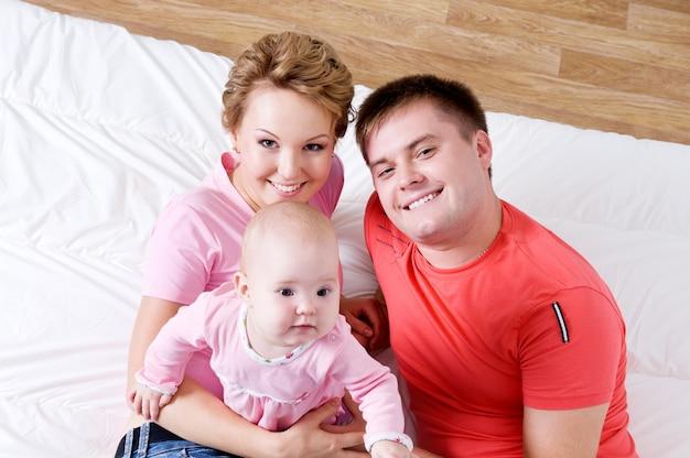 Портрет образа жизни красивой молодой счастливой семьи, лежа в постели у себя дома - высокий угол Бесплатные Фотографии