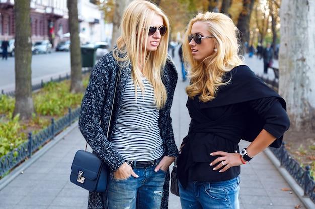 Портрет образа жизни двух лучших друзей блондинок, проводящих время в центре города в хороший осенний осенний день, с использованием смартфона, в солнцезащитных очках и модных модных образах. Бесплатные Фотографии
