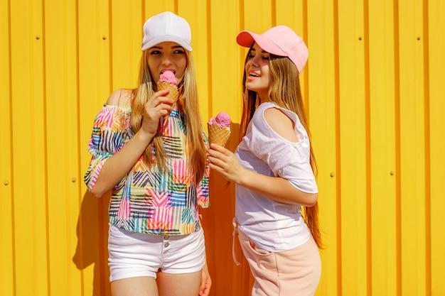 Lifestyle portrait of two beautiful best friend hipster lady wearing stylish bright outfits and having great time. standing near yellow wall enjoying day off and eating sweet cold ice-cream Premium Photo