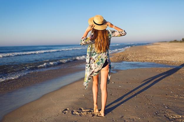 Stile di vita estate moda ritratto di bellezza donna bionda in posa sulla spiaggia solitaria, indossando bikini elegante pareo e cappello, guarda l'oceano, l'umore delle vacanze di lusso, colori dai toni luminosi. Foto Gratuite