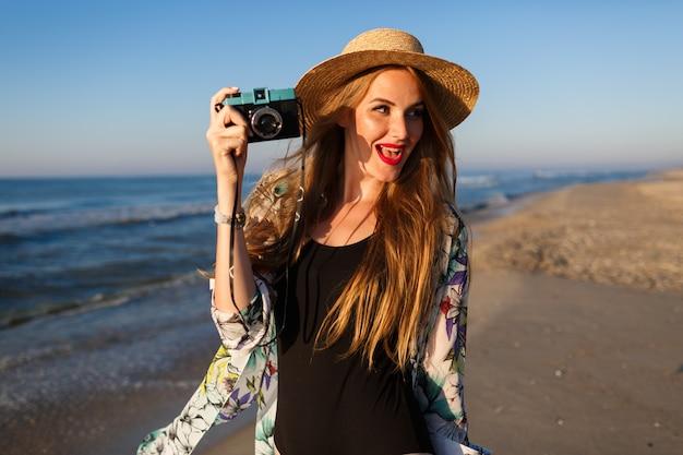 海の前の孤独なビーチの近くでポーズをとる若い美容写真家の女性のライフスタイルの日当たりの良い肖像画スタイリッシュなビキニの帽子のサングラスとパレオ、豪華な休暇の雰囲気。 無料写真