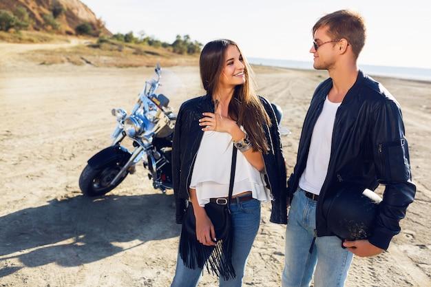 バイク-旅行の概念によってビーチで一緒にポーズをとって若いカップルライダーのライフスタイルの日当たりの良い肖像画。二人とバイク。驚くほどセクシーな女と男の話と笑いのファッション画像。 無料写真