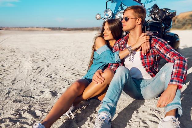 Ritratto soleggiato di stile di vita di giovani cavalieri delle coppie che si siedono insieme sulla spiaggia di sabbia in motocicletta - concetto di viaggio. due persone e bici. moda donna e uomo che abbraccia e sorride. Foto Gratuite