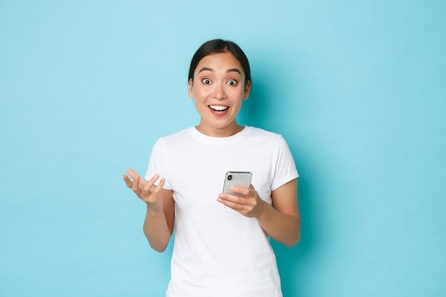Образ жизни, технологии и концепция электронной коммерции. удивленная счастливая азиатская девушка радуется большому объявлению в интернете, выглядит удивленно и любопытно, держа мобильный телефон на синем фоне. Premium Фотографии