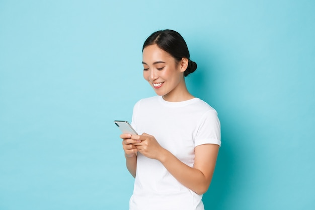 Lifestyle, technology and e-commerce concept. side view of attractive asian girl using mobile phone, texting, messaging or chatting with friends online, looking at smartphone screen pleased. Free Photo