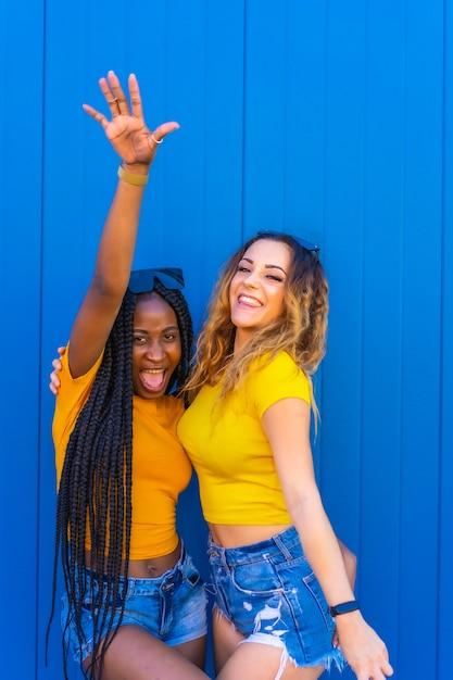 라이프 스타일, 노란색 티셔츠를 입은 파란색 벽에 사진 촬영을 즐기는 십대 여자 친구. 긴 머리 띠와 금발의 백인 여자 흑인 소녀. 프리미엄 사진