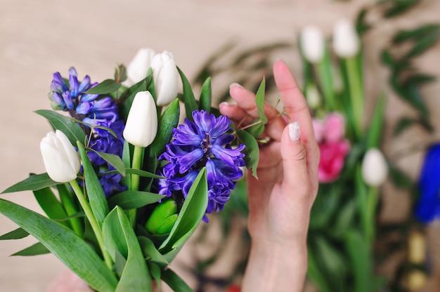 Садовник в цветочном магазине делает букет. lifestyle цветочный магазин. красивая цветочная композиция. деталь. Premium Фотографии