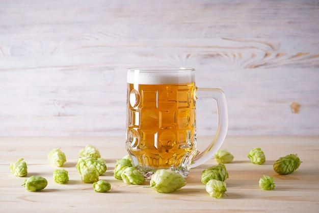 ガラスの軽いビールと木のスペースのホップコーン。 Premium写真
