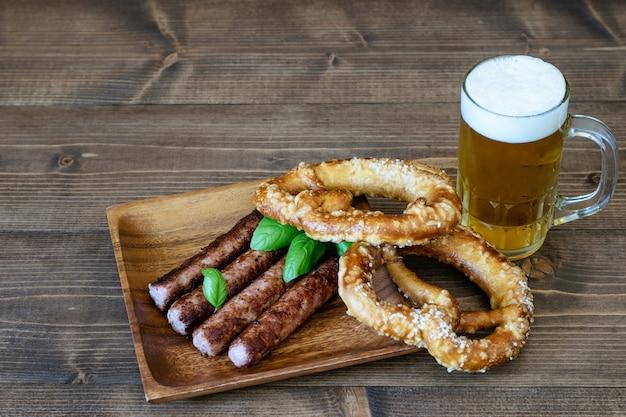 木製のフライドソーセージとプレッツェルを添えて軽めのビール Premium写真
