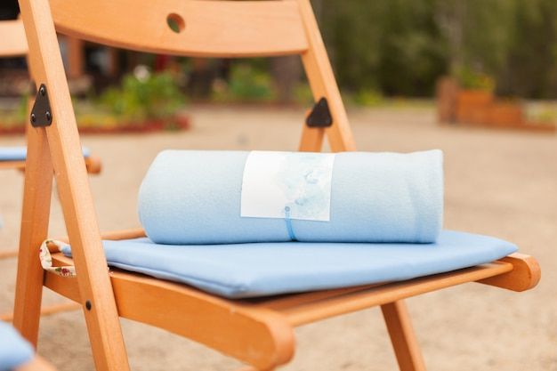 Light blue plaid on a brown chair, the concept of a warm wedding, close-up Premium Photo