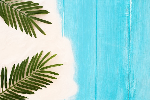 Light blue wooden background with sand and palm leaf, summer background Free Photo