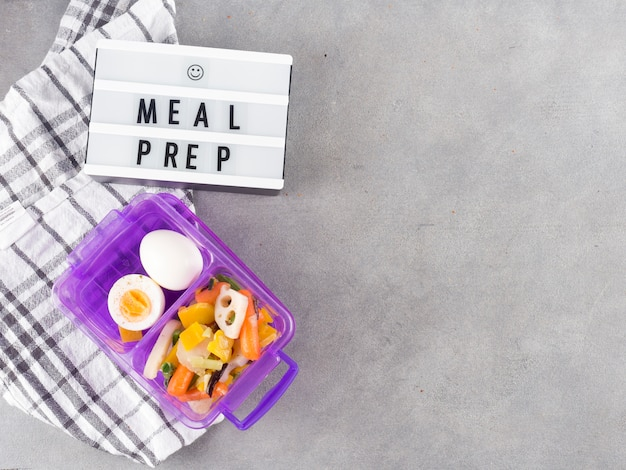 Light board with meal prep inscription near food in container Free Photo
