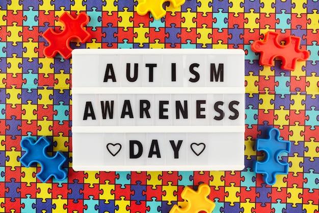 컬러 퍼즐 배경에 세계 자폐증 인식의 날 텍스트가있는 라이트 박스. 평면도 프리미엄 사진
