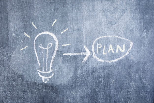 Light bulb and arrow pointing toward plan drawn on the chalkboard Free Photo